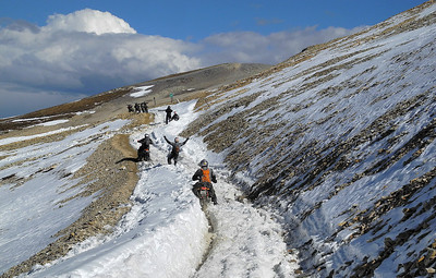 Riders help each other traverse a snowy path on Imogene Pass in Colorado.