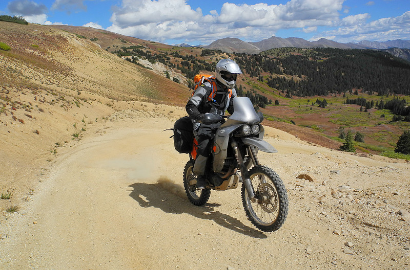 A rider wheelies up Taylor Pass near the summit in Colorado.