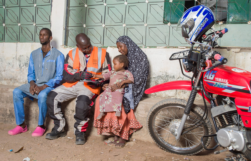 A medical worker, supported by Two Wheels for Life, providing front-line healthcare to a child in a remote village