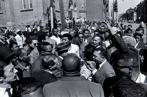 A crowd gathers as services let out of St. Benedict the Moor Church at what became Freedom Corner. Byrd Brown and others work to calm the people.