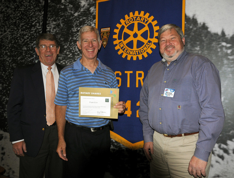 Rotary District Governor Tom Powell recognizes the Park City Rotary Club, including outgonig President Fr. Bob Bussen, as assistant governon Brian Gorum looks on.