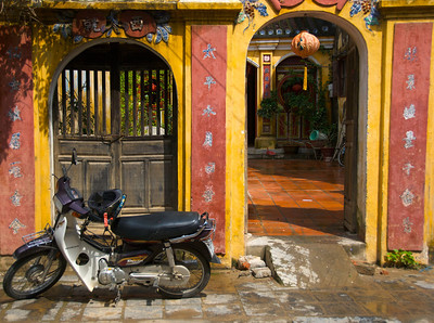 A motorbike in front of a colorful building in Hoi An, Veitnam