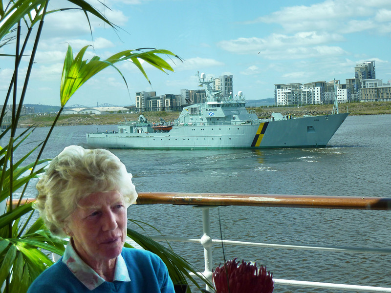 Mary dining on Royal Yacht with ship behind
