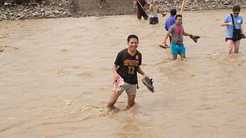 Pastor John wades through the river.