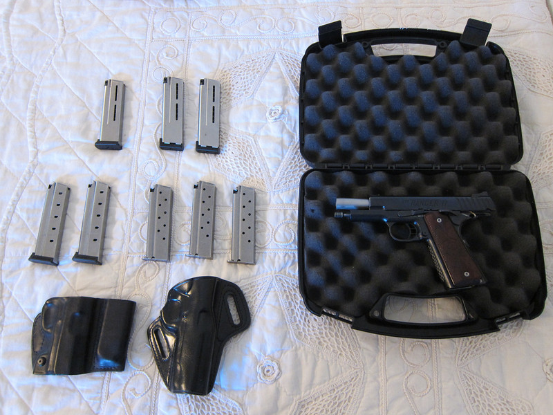 Comes with everything you see here, plus a takedown piece and manual under the foam, and two mag pouches I forgot about (see other pictures).  There are 3 OEM 8-round magazines, 2 10-round Tripp mags, and 3 Wilson Combat 10-round mags.  The holsters are by Blackhawk and Galco.