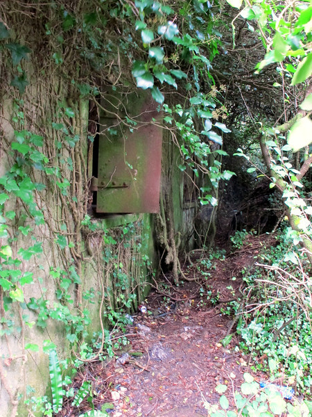 A substantial concrete building on the path, perhaps a wartime 'pill box' or lookout position.