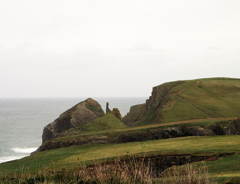 A passing runner in hi-vis jacket disappears up the hill to the cliff top at Melrope Rocks.   In the foreground is a smaller collapsed sea cave hole.