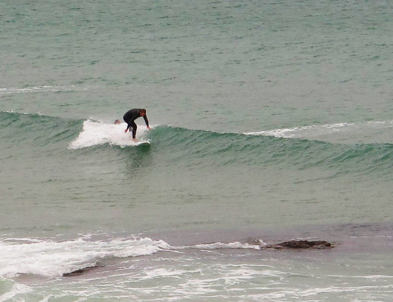 A surfer manages to stand in low swell at Harlyn Bay.