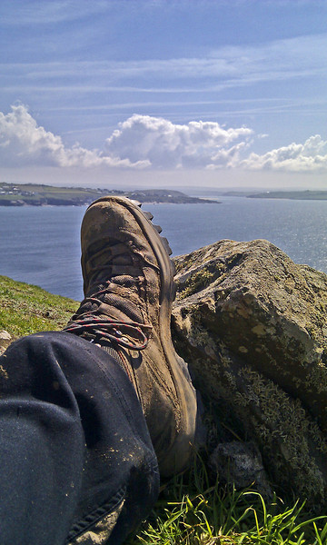 One of two weary feet resting against a rock near Rock with the camel Estuary beyond.