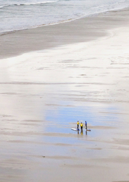 Surfers on the beach at Mawgan Porth deep in discussion.