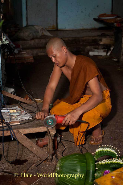 Monk Using Grinder to Cut Steel