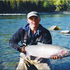 "Billy Labonte, guide at Silver Hilton Lodge on the Babine River, is holding the female steelhead, 40"" length, 24"" girth, 30# weight.  It took the small #6 Orange Babine Muddler making a nice V wake as it floated dry on the surface of the big ""Goose Pool"" on the Babine.  Billy is holding the fish for me to photograph rather than trade fish and camera keeping the fish out of the water longer than necessary.  September, 1998."