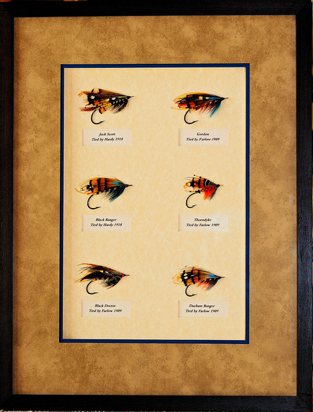 Shadow Box frame of six Salmon Flies.  These flies were tied back in 1909 and 1918 by the famous Houses of Farlow and Hardy Bros. for English salmon anglers journeying  to the great Atlantic Salmon Rivers in Norway.  These flies are large, size 3/0,  overall length is 2 1/2 inches and the eyes are braided gut material!  Yes, their value is considerably greater now than when they were tied.