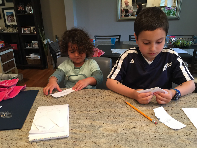 Sami and Koby making paper boats and airplanes