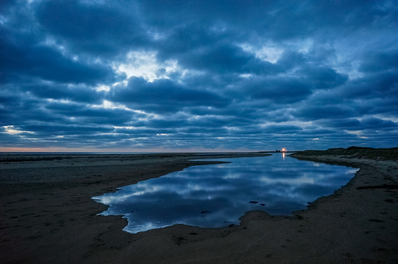 Race Point light reflecting in twilight tidal pool