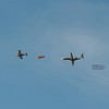 A closer view of the trio of planes flying in formation, with the Oracle aerobatic plane in the middle.