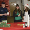 Firefighter Mark Adams accepts a cup of cider from Ramona Mikelson and Morgan Slaten with the Peninsula Youth Council