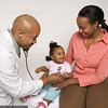 M220 / Choice 3 of 7 /<br /> <br /> African-American male doctor examining baby girl with mother watching.