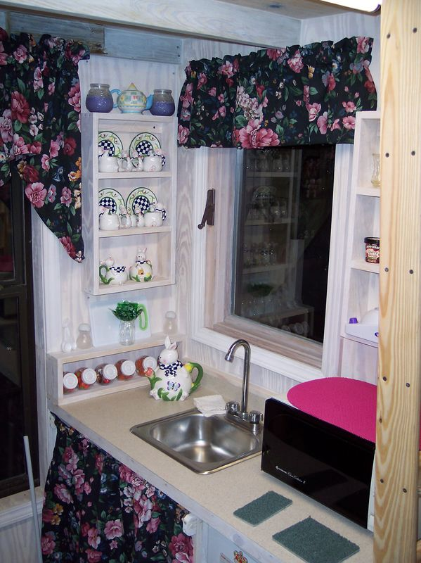 """Wow!  Darlene has already adorned the kitchen area with curtains.  Sarah's """"china cabnet"""" is open on the wall for easy viewing."""