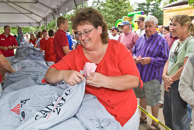 Track employee Colleen Weaver passes shirts to the gathered masses during the Sunday giveaway. Photo Eric Jenks 9/5/10