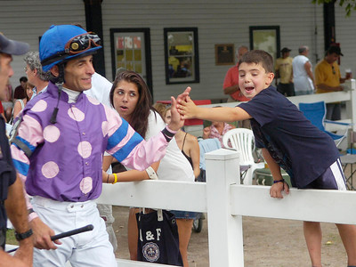 Jockey John Velazquez slaps five with eight year old Luca Mandato of Long Island as he heads for the paddock Friday. Ed Burke 9/3/10