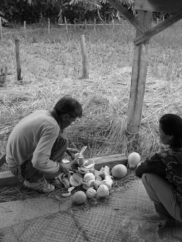 jaman and his wife sumi cutting up some freshly picked fruit on our hike through the rice villages around bario