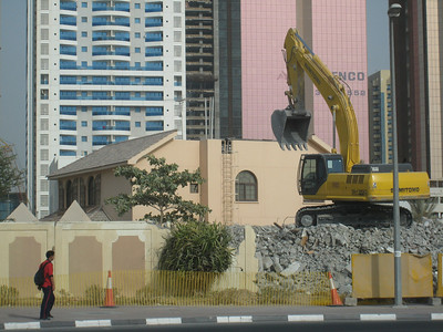A large house with the roof already removed and the bulldozers ready to go with the advancing tide of high rises in the background.