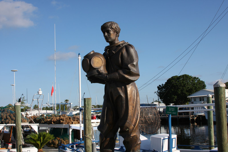 Tarpon Springs is the sponge capitol of the world (so the sign says). Many decades ago the was a sponge blight in Greece that killed most of the sponges. The sponge fishermen, without a livelihood, were easily persuaded to move to Tarpon Springs where sponges were and are still plentiful. This statue depicts the old traditional sponge diving suit. The feet were weighted so the diver could walk across the ocean floor picking sponges. He would place them into a basket like the one you see on the boat behind him. Oxygen was pumped from the surface to the diver through air hoses. Behind the stature is a sponge boat loaded with sponges. They'll be cleaned, clipped, and prepared for auction where they'll be sold.