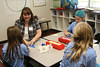 Ascension students learn to fold origami Blue Gators with one of ESA's fifth grade teachers, Claire Alvarado.