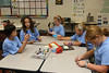 Ascension students putting the finishing touches on their origami Blue Gators.