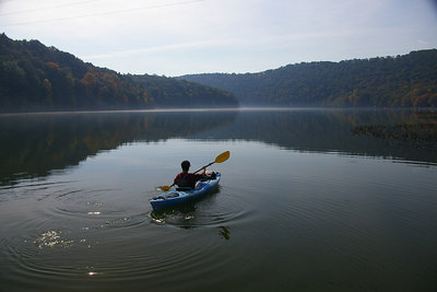 A lone kayaker enjoys a warm Autumn day on the Schuylkill River in the Auburn Desilting Dam near Landingville, Pennsylvania