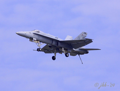 F-18 on a slow pass with landing gear and arresting hook down.