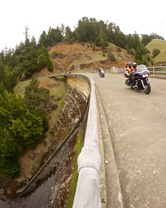 Bikers ride across Alpine Lake Dam ref: 78f86ff8-8499-46f5-a1e2-8b744dc9ee41