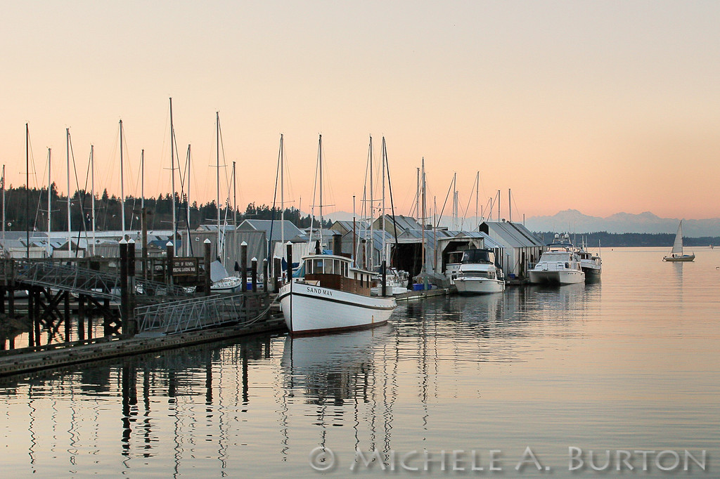 Early evening on Budd Inlet in Olympia. The century-old tug Sandman is moored with other boats at Percival Landing.