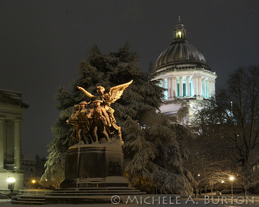 The Winged Victory Monument, honoring those who served in World War I, with the Washington State Capitol dome in the background. A light dusting of snow covers the dome in this night photo.