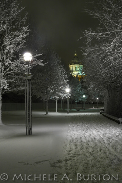 Many sets of footprints mark the snowy pathway around Capitol Lake in Olympia during a rare snowstorm. The Capitol Building is seen in the distance.