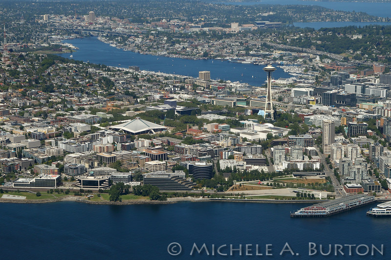 Aerial View of Seattle looking north from Elliott Bay toward Lake Union and the University of Washington. The Space Needle and Seattle Center are in the foreground.