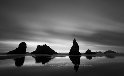 Daggers and Dark Thoughts.  Long exposure.  I took this shot in one of two evenings I spent at the shore at Bandon. High winds blew the clouds from North to South, making their movement quite remarkable to me, while it was quite calm at the surface, enabling me to capture the motion over several seconds of exposure. The tiny white light in the sky is planet Venus. Beware of tidal pools in that place though, I've heard of some inattentive people getting an undesired evening bath in the darkness...