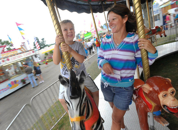 Laura Glass of Portage,right, takes her nephew Joey Loebig,4, of Cheswick, on the carousel at teh Cambria County Fair in Ebensburg,PA., Monday, Sept.3, 2012. (AP Photo/Tribune-Democrat, John Rucosky).