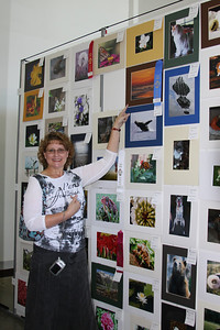 Carol Cox pointing to her winning photo, first place in the nature category at the Delta Fair.