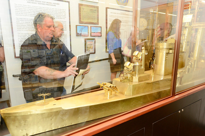 Jim McGrew of Columbia, SC., makes images of  USS Albany brass model exhibit at Albany County Convention and Visitors Bureau during ribbon cutting ceremony Monday, September 9, 2013 in Albany, N.Y.. McGrew served on the USS Albany 1976-79 and made the wood display case for the brass model. (J.S.CARRAS/THE RECORD)