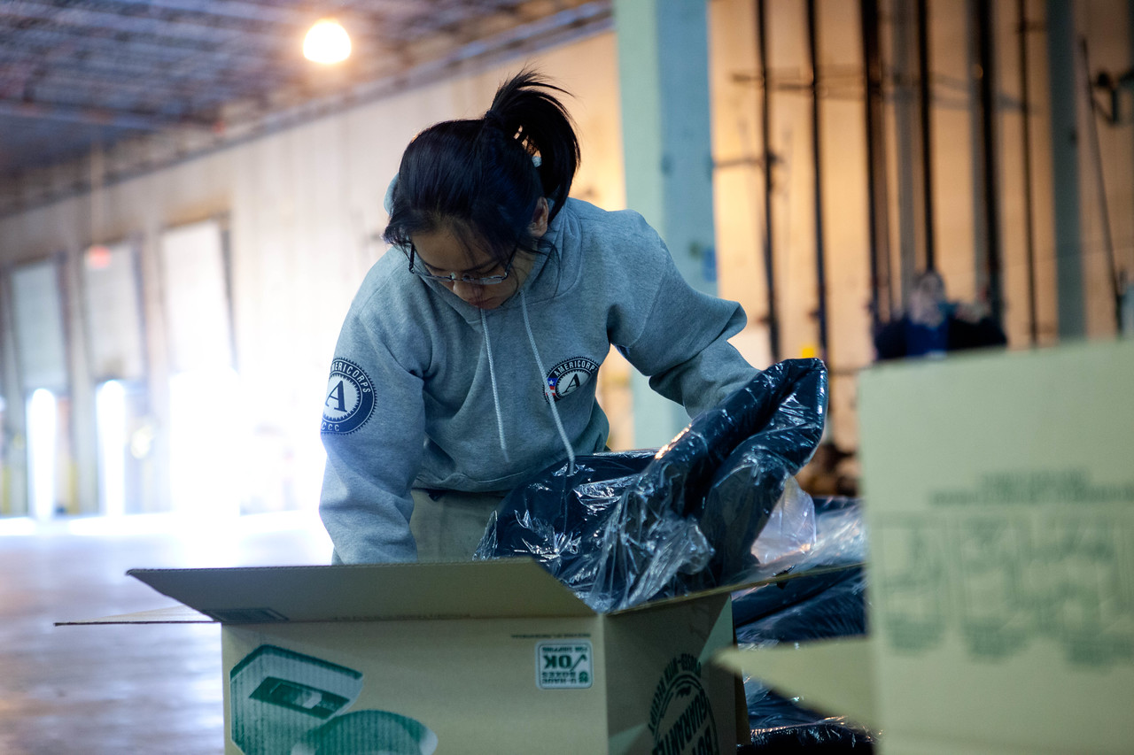 An AmeriCorps member packs winter coats for Hurricane Sandy survivors at the supply distribution center in Somerset, NJ. (Corporation for National and Community Service photo)