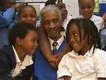 Foster Grandparent Program member Percy Thomas poses for a photo with some of the children he works with at Miner Elementary School in Washington, DC.