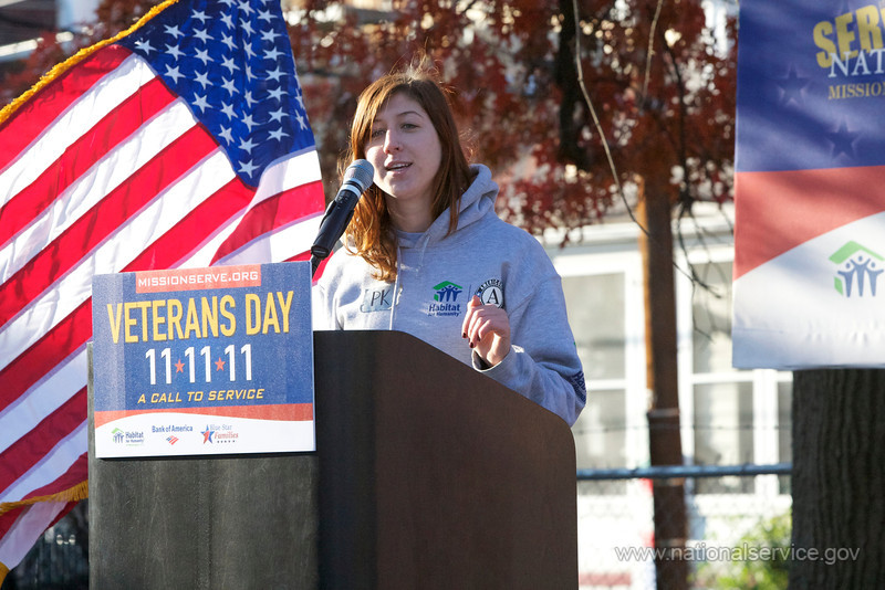 An AmeriCorps member with Habitat for Humanity speaks at a Veterans Day service event organized by Mission Serve and sponsored by Bank of America. AmeriCorps members worked alongside volunteers from Blue Star Families and the local community to build homes in the Ivy City neighborhood in Washington DC on November 11, 2011.