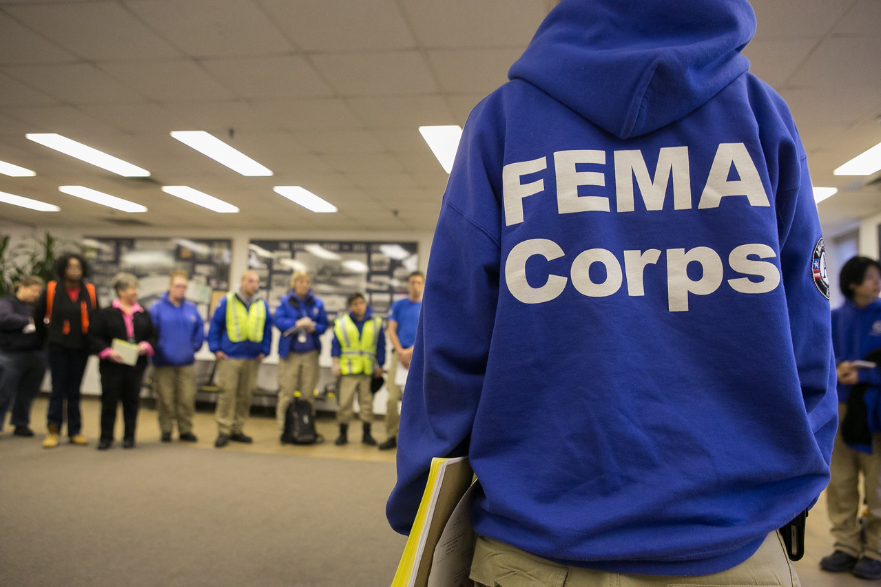 A FEMA Corps team assembles for their morning briefing at Farmingdale Airport in East Farmingdale, NY. FEMA Corps team members are working to assist residents impacted by Hurricane Sandy. (FEMA photo by Chris Ragazzo)