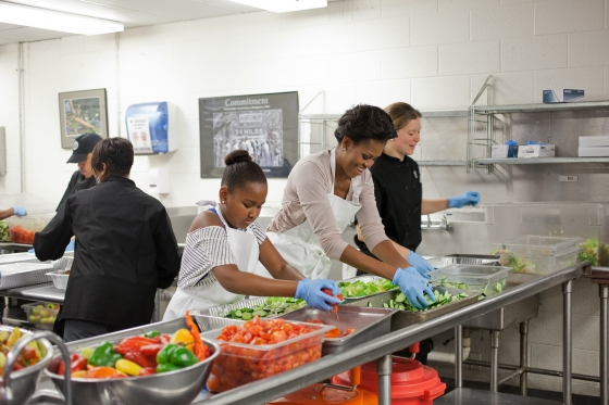First Lady Michelle Obama and daughter Sasha Obama participate in a service event preparing food at DC Central Kitchen in Washington, D.C., Sept. 10, 2011. (Official White House Photo by Samantha Appleton)