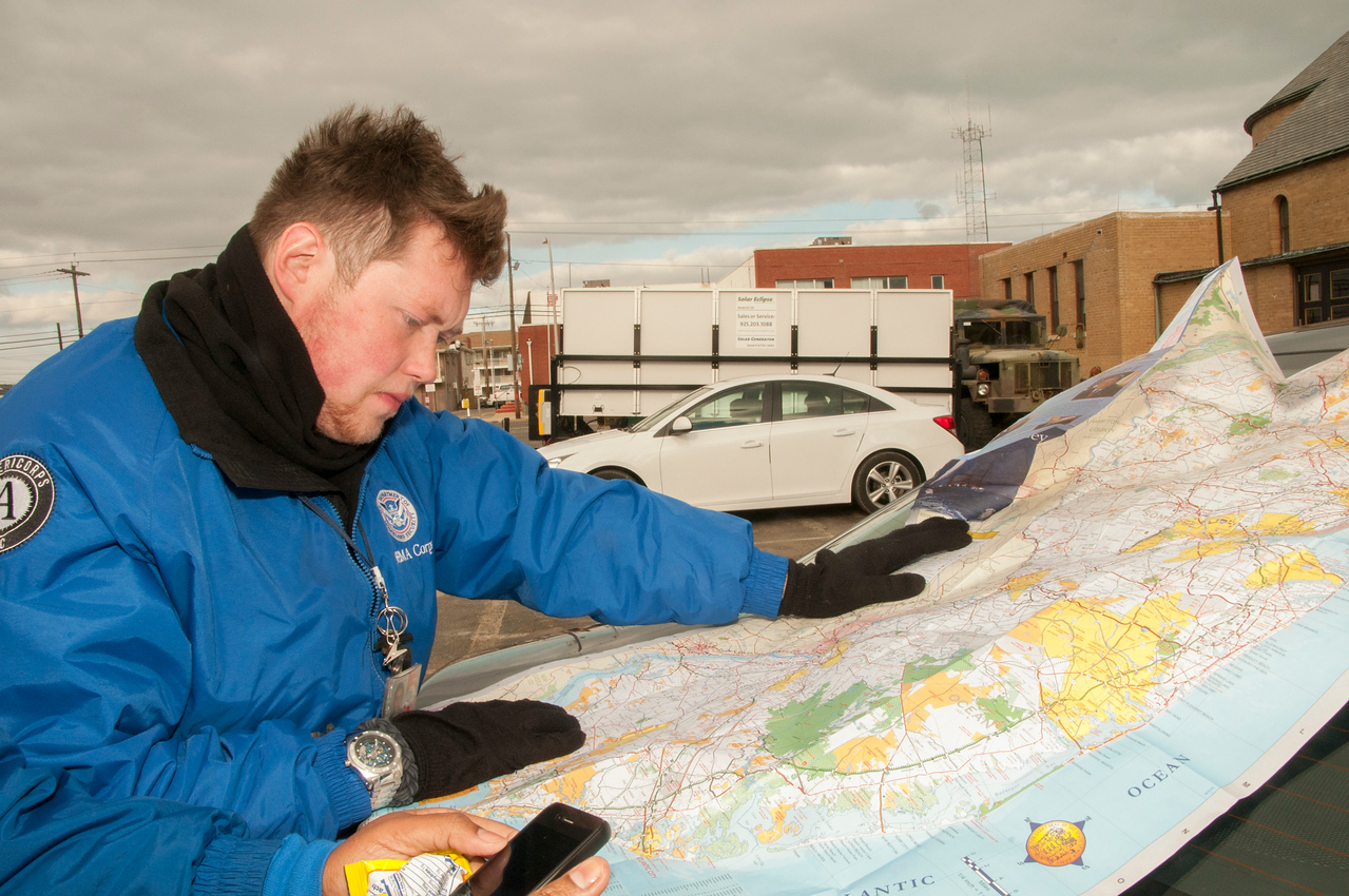 Seaside Heights, NJ -- FEMA Corps member Bryan Adams looks at a New Jersey map on Nov. 24, 2012, to plan the areas where he and other FEMA Corps members will work to provide assistance to residents in the coastal towns affected by Hurricane Sandy.  (FEMA photo by Patsy Lynch)