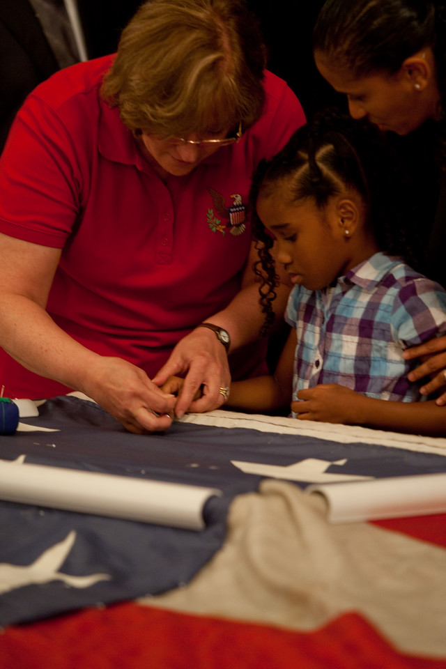 A volunteer helps a child add a stitch to the National 9/11 Flag at its visit to Capitol Hill on July 14, 2011.