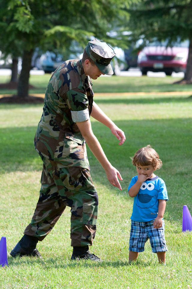 A U.S. Marine encourages a child to join in the fun during a 2011 Let's Read Let's Move event in Quantico, VA.