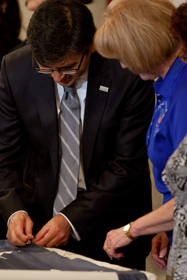 CNCS Acting CEO, Robert Velasco, II, adds a stitch to the National 9/11 Flag during the flag's visit to Capitol Hill on July 14, 2011.